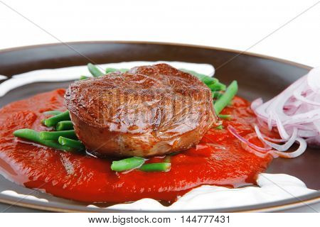 pork medallion served on tomato sauce with green peas on dark plate isolated on white background