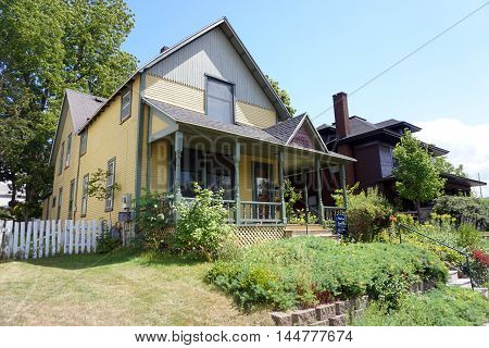 PETOSKEY, MICHIGAN / UNITED STATES - AUGUST 5, 2016: A yellow Victorian home with a wraparound porch on Division Street near downtown Petoskey, Michigan.