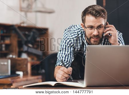 Jeweler in an apron talking on a cellphone and taking notes while working on a laptop at a bench in his workshop