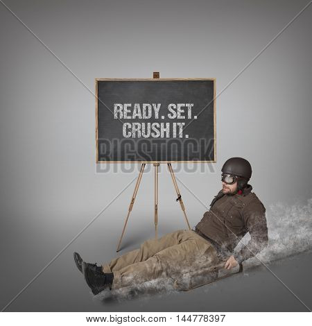 Ready Set. Crush it text on blackboard with businessman sliding with a sledge