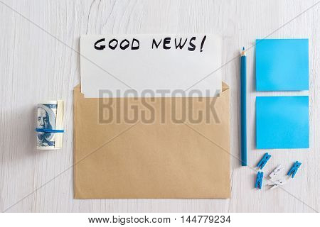 Greeting card in envelope with blank paper and good news text. Top view on greeting set on table with blue pencil, stickers, pins and money. Congratulation mockup
