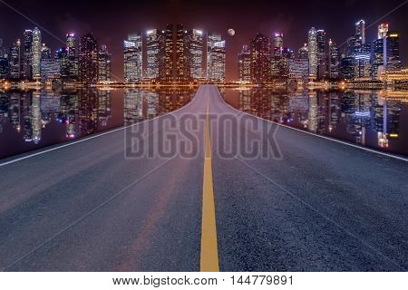 Lane blacktop in the colorful night cityscape with beautiful skyscrapers background.