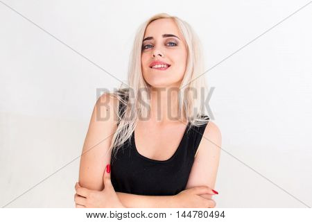 Confident beautiful woman in black dress biting her lip. Young attractive blonde with folded arms looking at camera with arrogant expression, white background