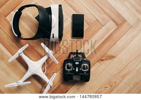 Virtual reality glasses and drone, free space, flat lay. Top view on quadrocopter with remote control and vr headset with smartphone on wooden background, copy space.