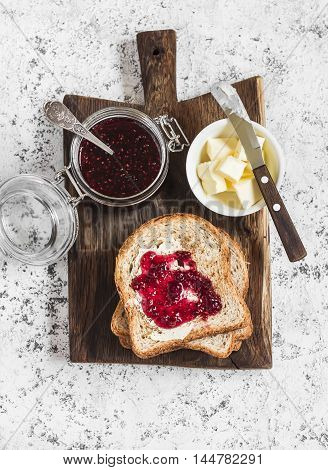 Jam butter toast bread on wooden cutting board on a light background. Top view