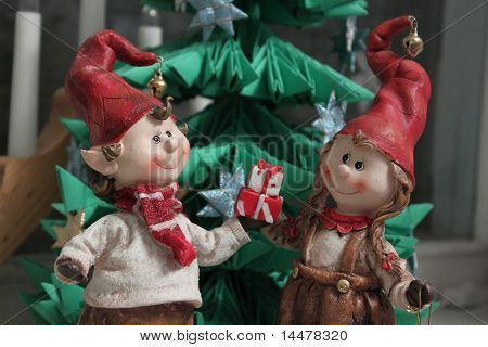 Christmas Elfs Boy And Girl Giving A Present Under Christmas Tree  (horizontal)