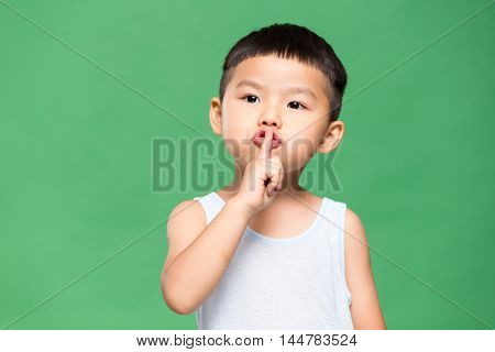 Little kid putting a finger on his lips