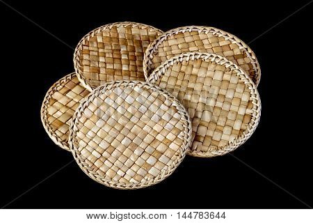 Rattan coasters or drinks mats isolated against a black background