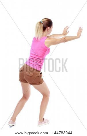 back view of woman pushes wall. Isolated over white background. Sport blond in brown shorts pushing something on the side.