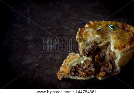Homemade Steak and Cheese Pie Sliced on Rustic Baking Tray Copy Space Horizontal