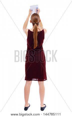 back view of stands woman takes notes in a notebook. girl watching. Isolated over white background. Slim blonde in a burgundy dress writes in a notebook.