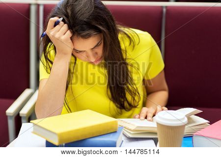 education, high school, university, learning and people concept - bored student girl with coffee reading book on lecture