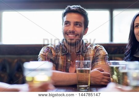 people, leisure, friendship and communication concept - happy man with friends drinking beer and watching sport game or football match at bar or pub