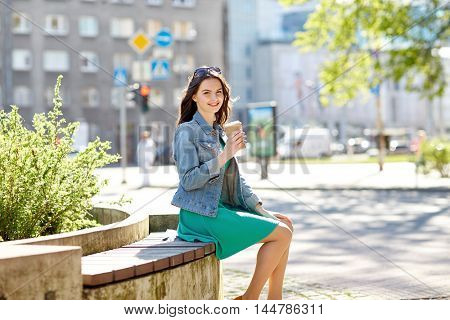 drinks and people concept - happy young woman or teenage girl drinking coffee from paper cup sitting on on city street bench