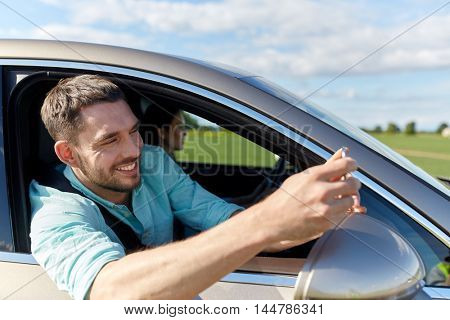 road trip, transport, travel, technology and people concept - happy smiling man with smartphone driving in car and taking selfie