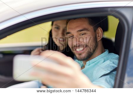 road trip, leisure, couple, technology and people concept - happy man and woman driving in car and taking selfie with smartphone