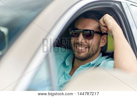road trip, transport, travel and people concept - happy smiling man in sunglasses driving car