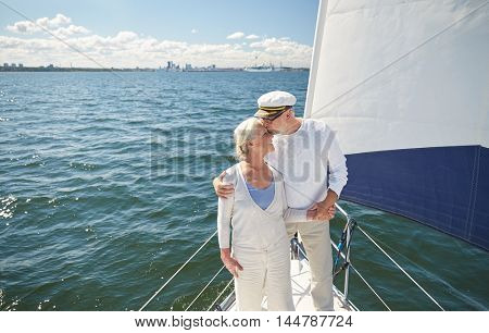 sailing, age, tourism, travel and people concept - happy senior couple kissing on sail boat or yacht deck floating in sea