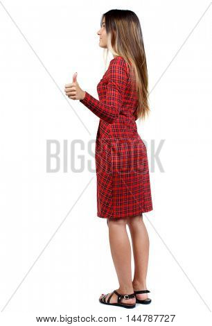 Back view of woman thumbs up. girl in red plaid dress standing cancer and shows thumb up.