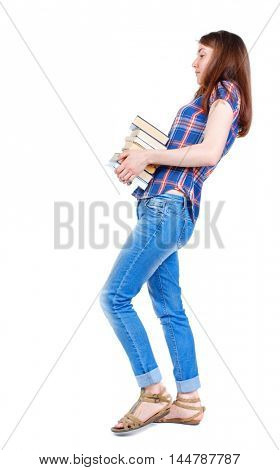 Girl comes with stack of books. side view. Girl in a plaid shirt goes to the side with a stack of heavy books.