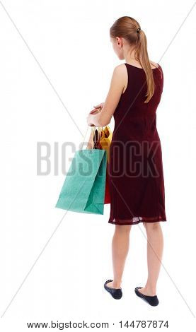 back view of woman with shopping bags. Isolated over white background. Slim blonde in a burgundy dress holding shopping bags.