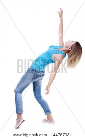 Balancing young woman. or dodge falling woman. blonde in a blue shirt and jeans leans back.