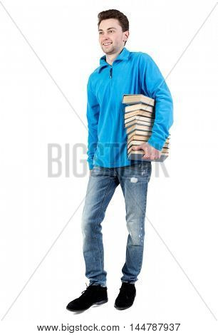 side view of going man carries a stack of books. curly-haired student in a blue warm jacket is smiling to meet us and carries the book.