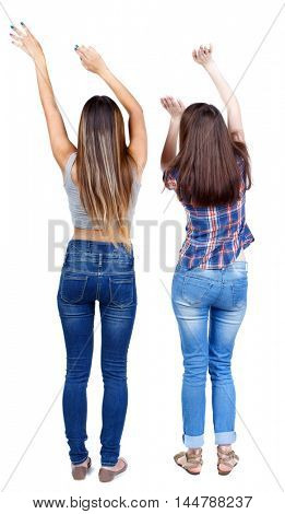 Back view of two dancing young women. Dance party. girls teens dance, enjoy and express positive emotions and having fun. Two young girls in jeans waving his hands to the music.