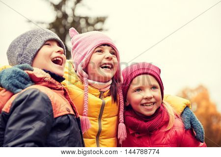 childhood, leisure, friendship and people concept - group of happy kids hugging and laughing in autumn park
