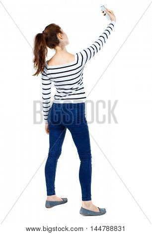 back view of standing young beautiful woman using a mobile phone. girl watching. Girl in a striped sweater makes selfie.
