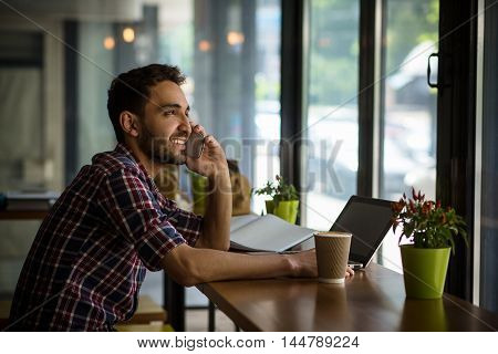 Profile of handsome man working in restaurant. Happy man talking over mobile or smart phone, looking at window while sitting in front of laptop computer.