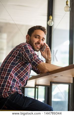 Business or freelance concept. Low view of handsome man speaking over mobile or smart phone while working in restaurant or cafe.