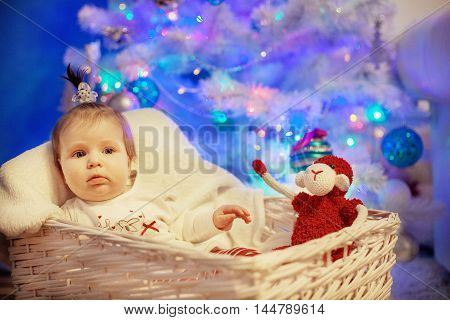 infant lying near the tree. The concept of New Year and Christmas