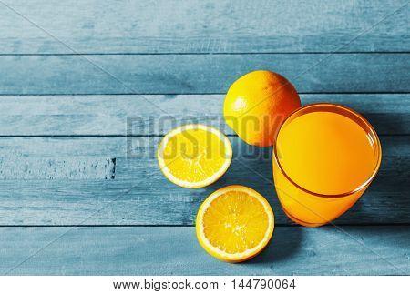 Orange juice and fresh orange on vintage wooden table in still life tone
