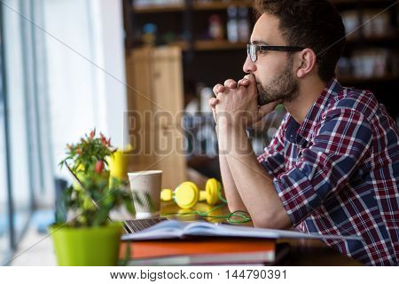 Profile of serious handsome freelance man in glasses working in restaurant or cafe. Man looking at window and thinking about something.