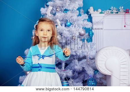 beautiful little girl in a dress near the tree. The concept of New Year and Christmas