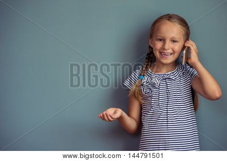 Cute little girl in dress is talking on the mobile phone looking at camera and smiling standing on gray background
