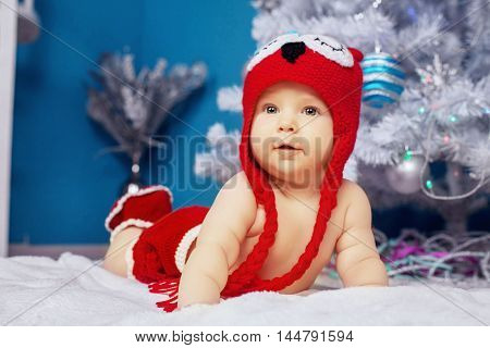 merry sweet little baby lying near the tree. The concept of New Year and Christmas