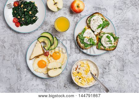 Breakfast table with different healthy food. Fried eggs salad of spinach leaves oatmeal with milk cheese sandwiches avocado poached eggs apples and orange juice top view