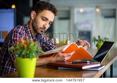 Portrait of handsome student reading book or document while studying in restaurant or cafe. Man using laptop computer for preparation to exams or classes.