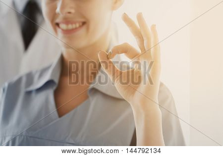 gesture, people and medicine concept - close up of happy female doctor or nurse showing ok hand at hospital