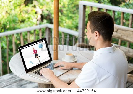 sport, people and technology concept - man with fitness application on laptop typing outdoors on summer terrace and drinking coffee