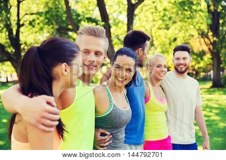 fitness, sport, friendship and healthy lifestyle concept - group of happy teenage friends or sportsmen hugging and talking outdoors