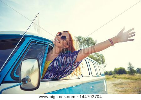 summer holidays, road trip, vacation, travel and people concept - smiling young hippie woman driving minivan car and waving hand