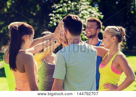 fitness, sport, friendship and healthy lifestyle concept - group of happy teenage friends or sportsmen making high five outdoors