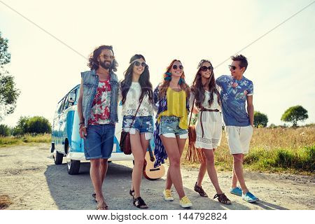 summer holidays, road trip, vacation, travel and people concept - smiling young hippie friends walking over minivan car