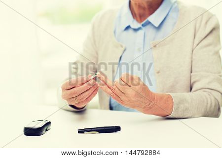 medicine, age, diabetes, health care and people concept - close up of senior woman with glucometer checking blood sugar level at home