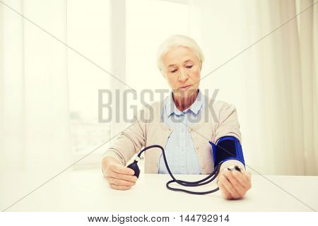 medicine, age, health care and people concept - senior woman with tonometer checking blood pressure level at home