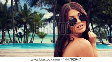 summer vacation, tourism, travel, holidays and people concept -face of young woman with sunglasses over tropical beach with palms and swimming pool background