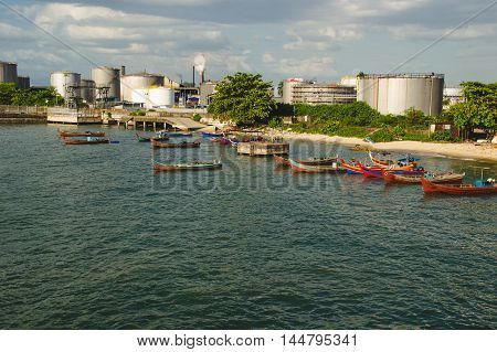Photo of the Factory or plant near water with boats. Industrial district Malaysia